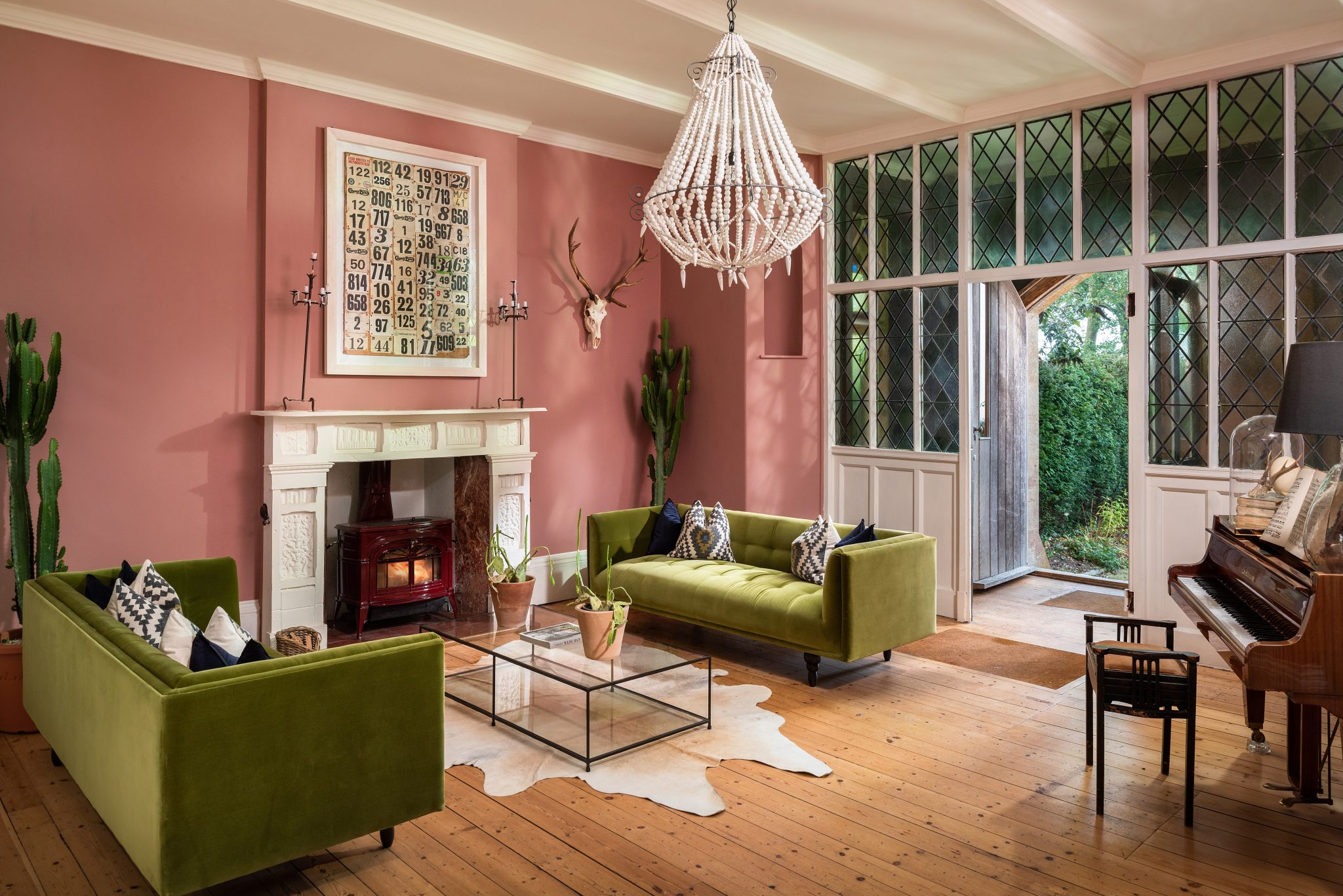 Pink wall living room with green sofas at Zingara holiday rental in Devon