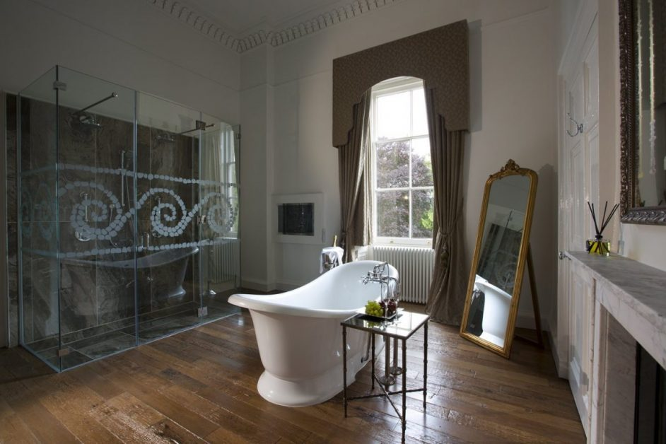 A freestanding white bath in front of a window with grapes next to it at the Bailbrook House hotel in Bath.