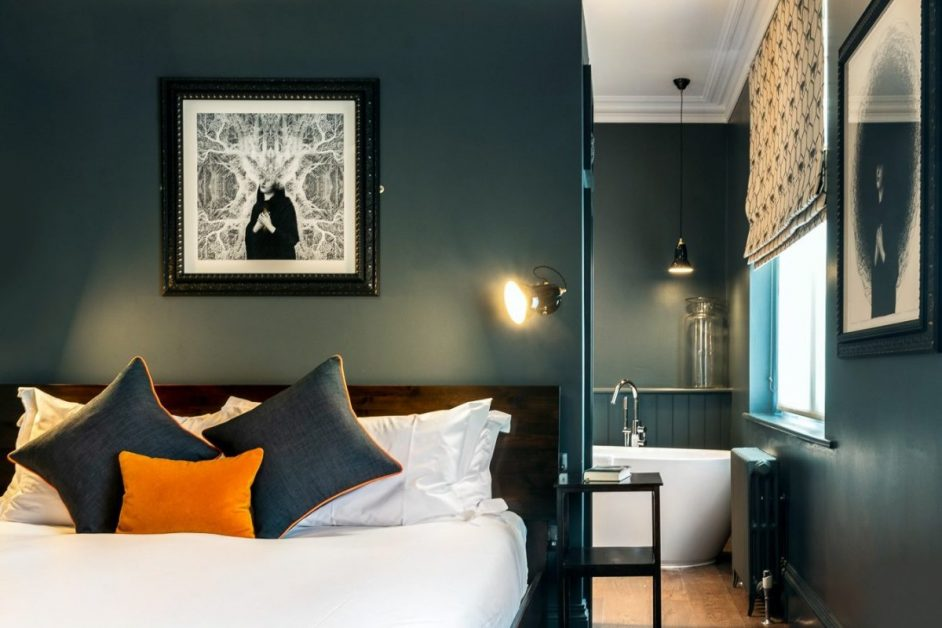 Boutique bedroom with black and white framed picture on the wall and freestanding bath seen in the background at the Ginger Pig hotel, Hove in Brighton