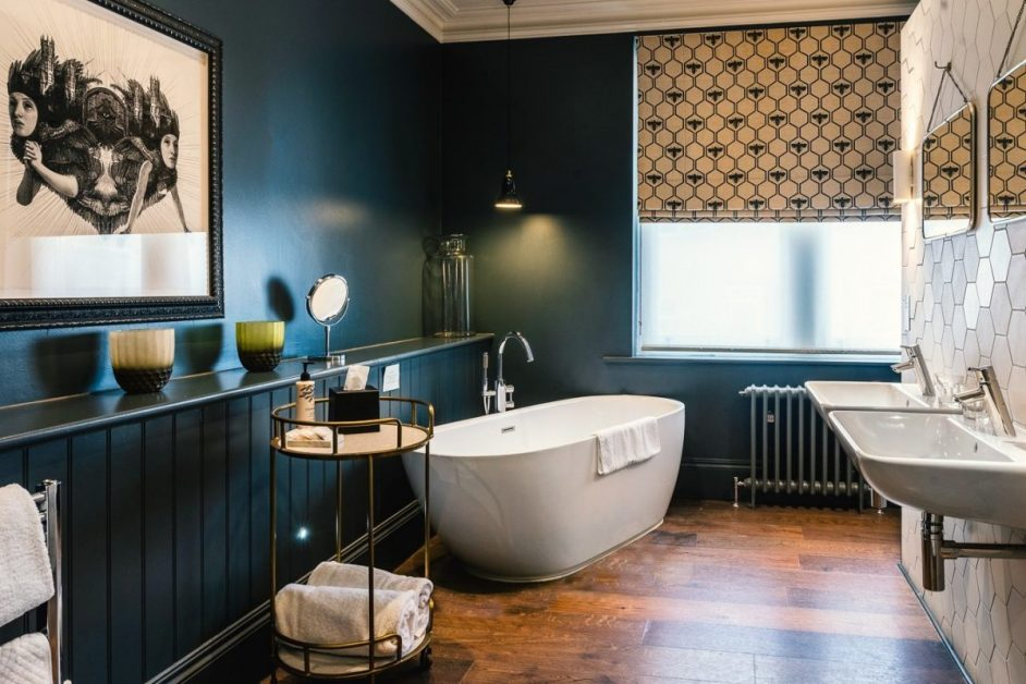 A freestanding white bath tub in an arty room with dark walls at the Ginger Pig boutique hotel in Hove, Brighton