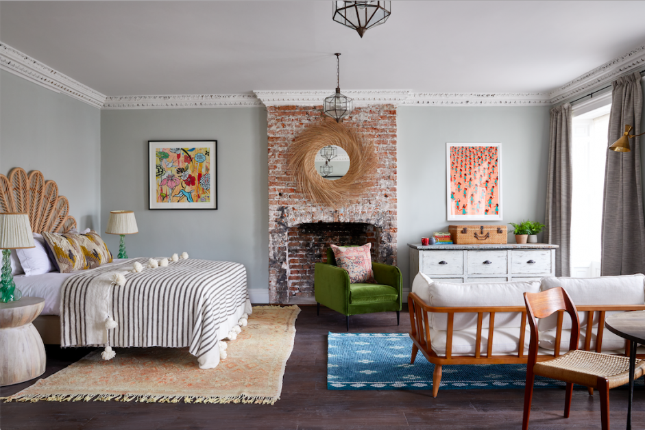 A bedroom with bed, brickwork fireplace and seating area at Artist Residence Bristol boutique hotel.