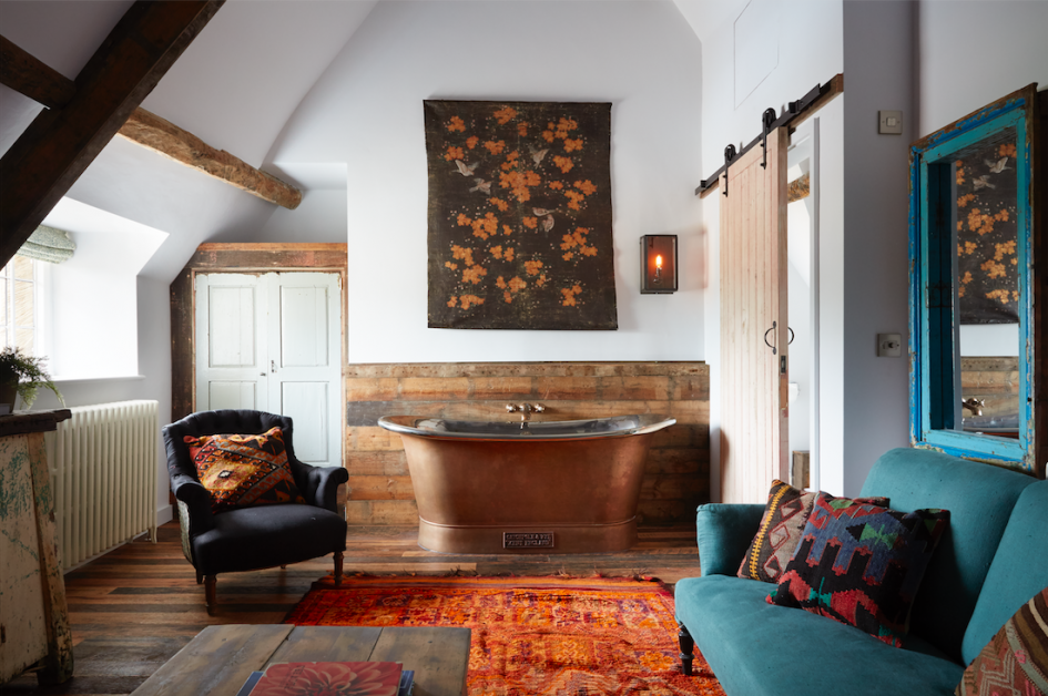 A copper bath next to a sofa and chair in the luxury Farmhouse Suite at Artist Residence Oxfordshire hotel.