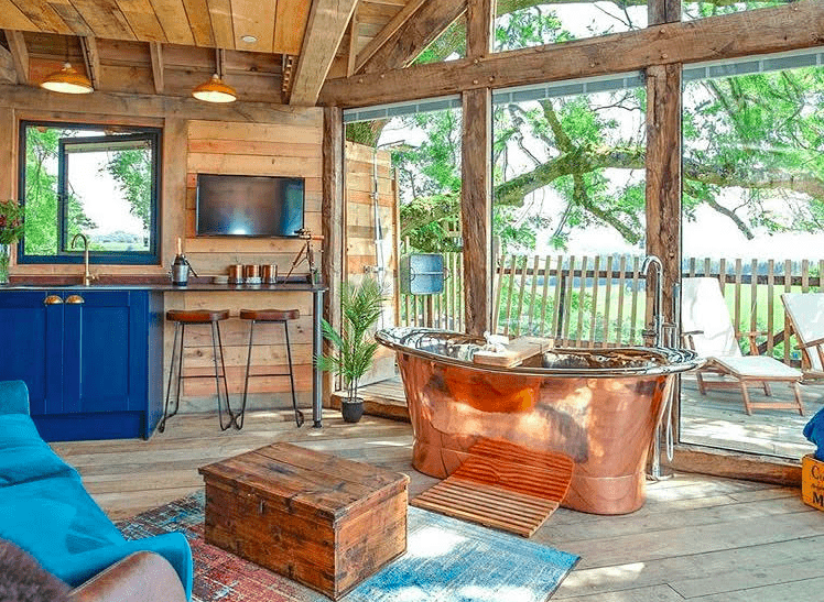 Copper bathtub in the window at the Squirrels Nest glamping treehouse in Powys, Wales.