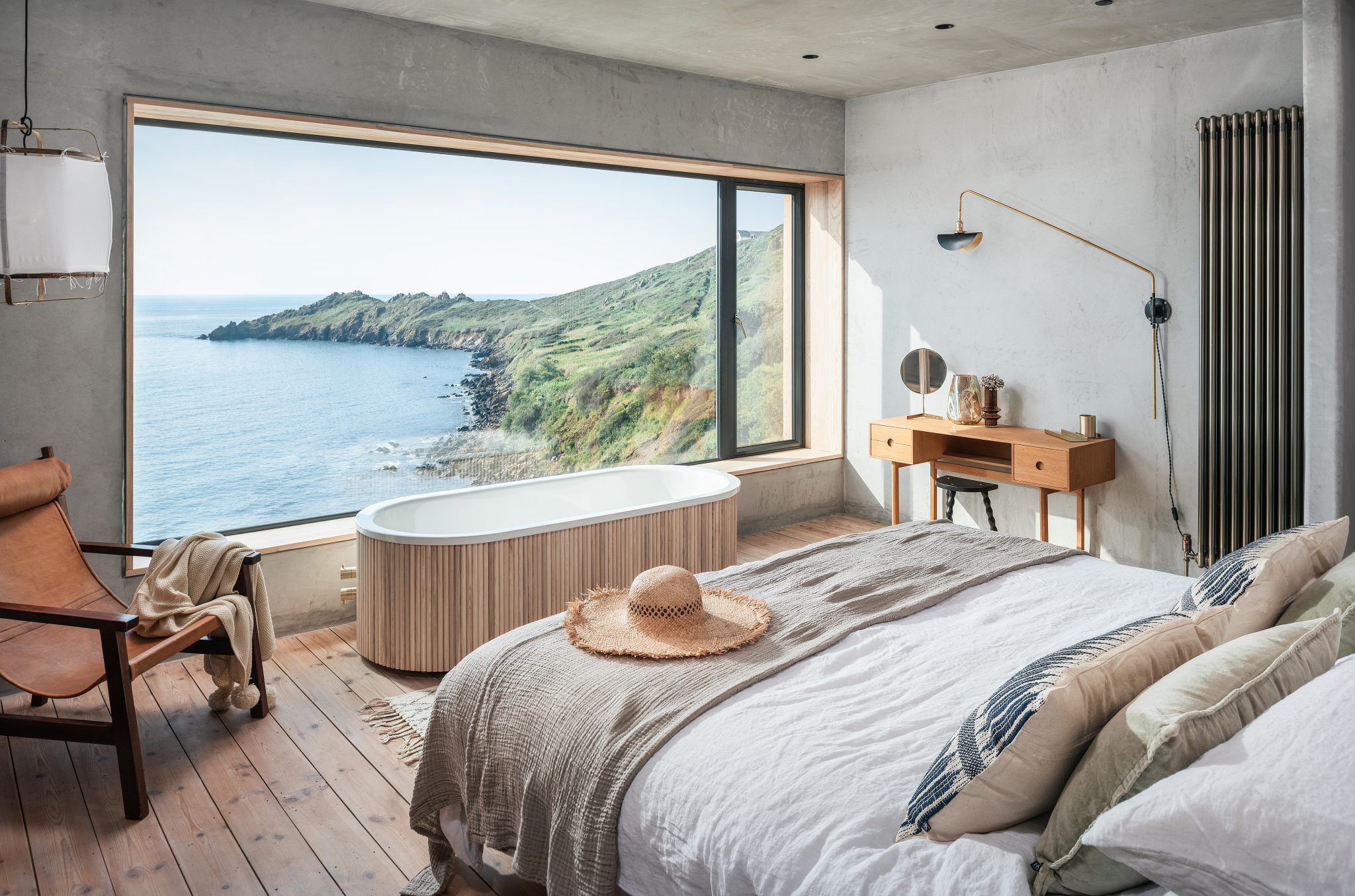A bath in front of a window in a minimalist bedroom at Ukiyo Beach House in Cornwall.