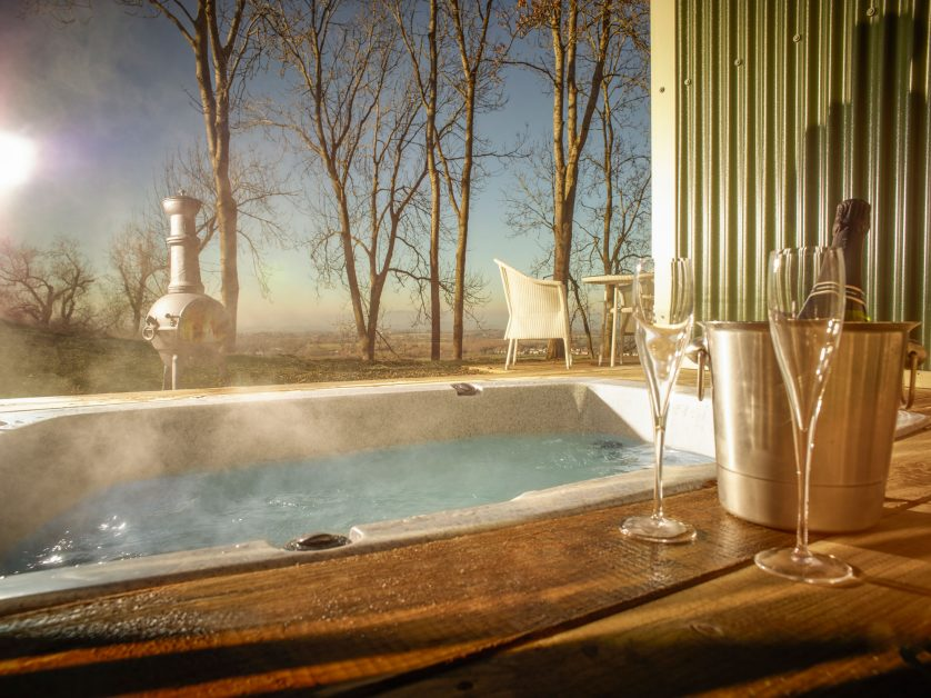 Hot tub with bottle of champagne on the side at Fish Hotel Cotswolds