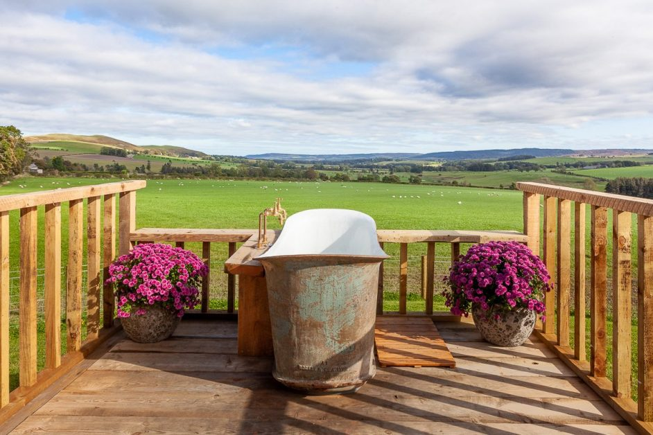 Outdoor bath with stunning view of rolling green countryside