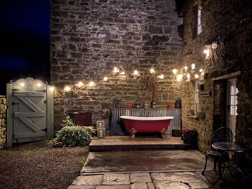 red bath tub outside with fairy lights above