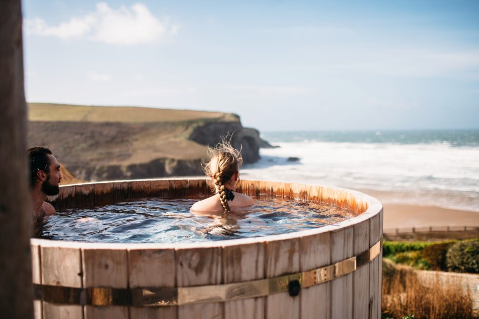 Woman looking out to sea from the clifftop hot tubs at The Scarlet Hotel in Newquay.