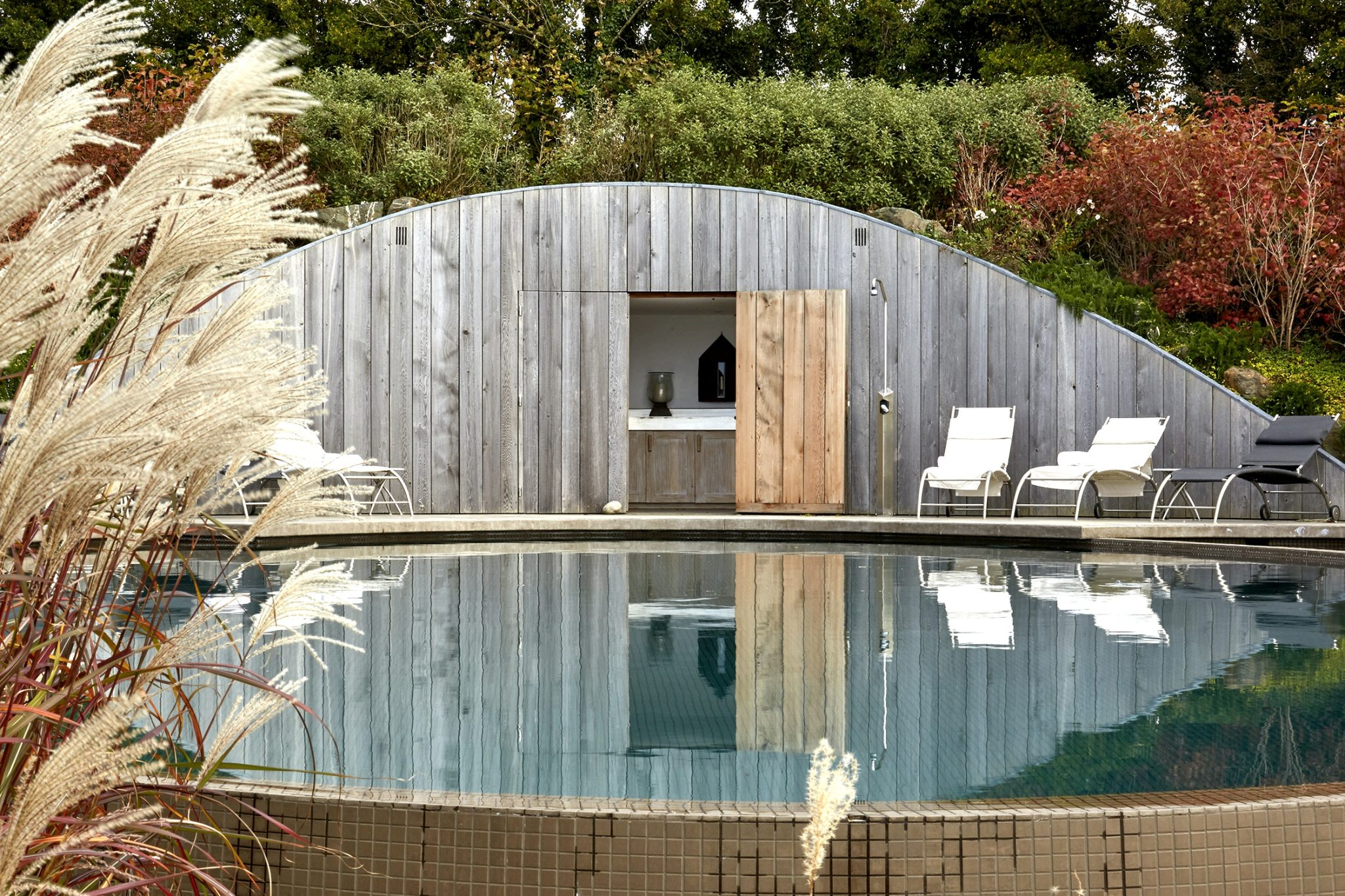 swimming pool with sun loungers and outdoor bar at Cornish holiday home