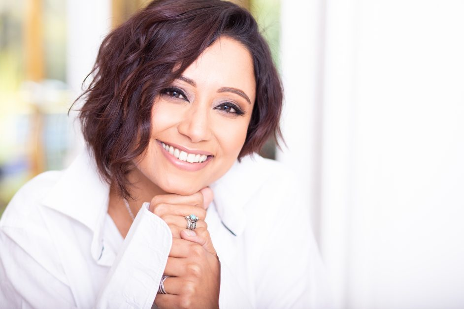 Home spa expert and skincare therapist Ez Dyer smiling in a headshot with her tousled hair and wearing a white shirt