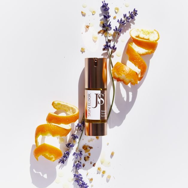 Home spa beauty product Janet Scrivner Skin Elixir in gold bottle with lavender and orange peel surrounding it