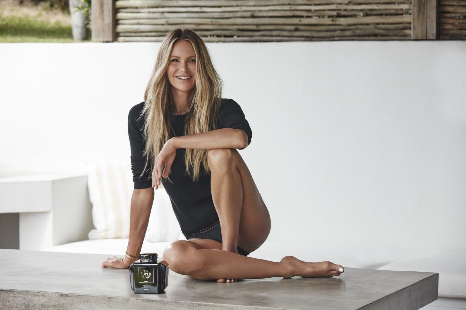 Supermodel Elle Macpherson sitting down wearing a black T-shirt and bikini bottoms next to a bottle of The Super Elixir from her beauty brand, WelleCo