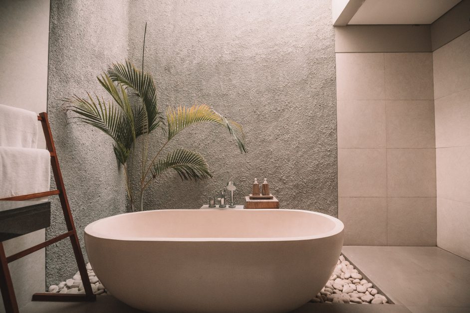 At home spa: Freestanding bath tub in a luxury bathroom with a palm plant behind it.