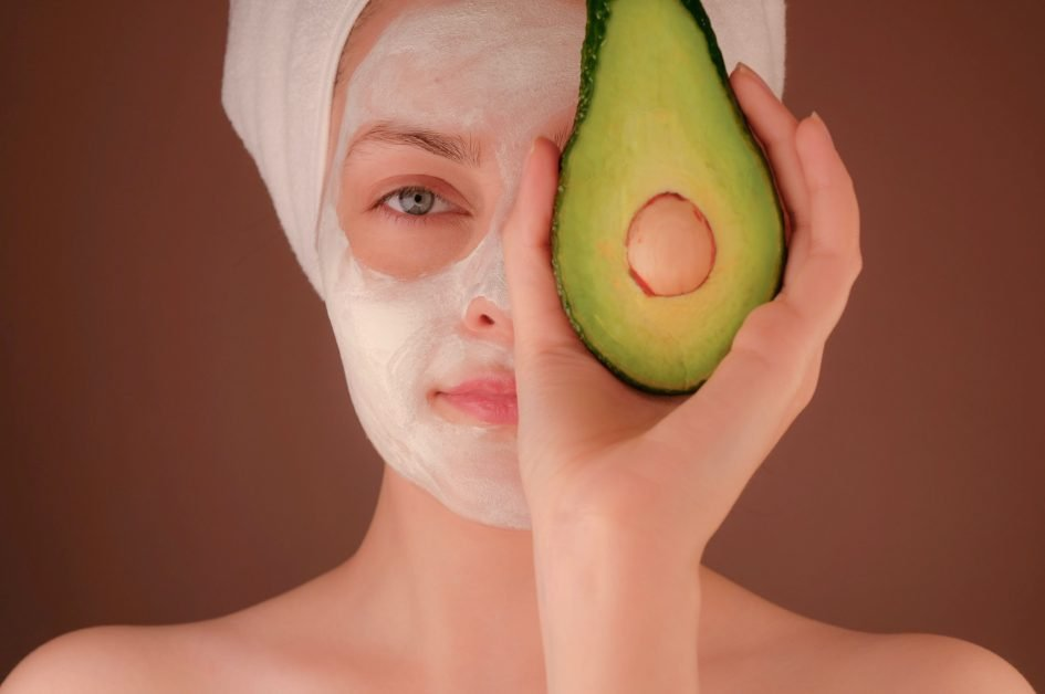 At home spa: Woman in a white beauty face mask holding an avocado up to cover her right eye.