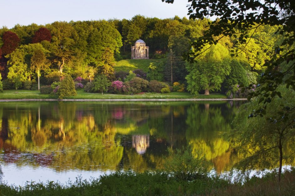 The Temple of Apollo reflected in the lake at Stourhead, Wiltshire, in May.